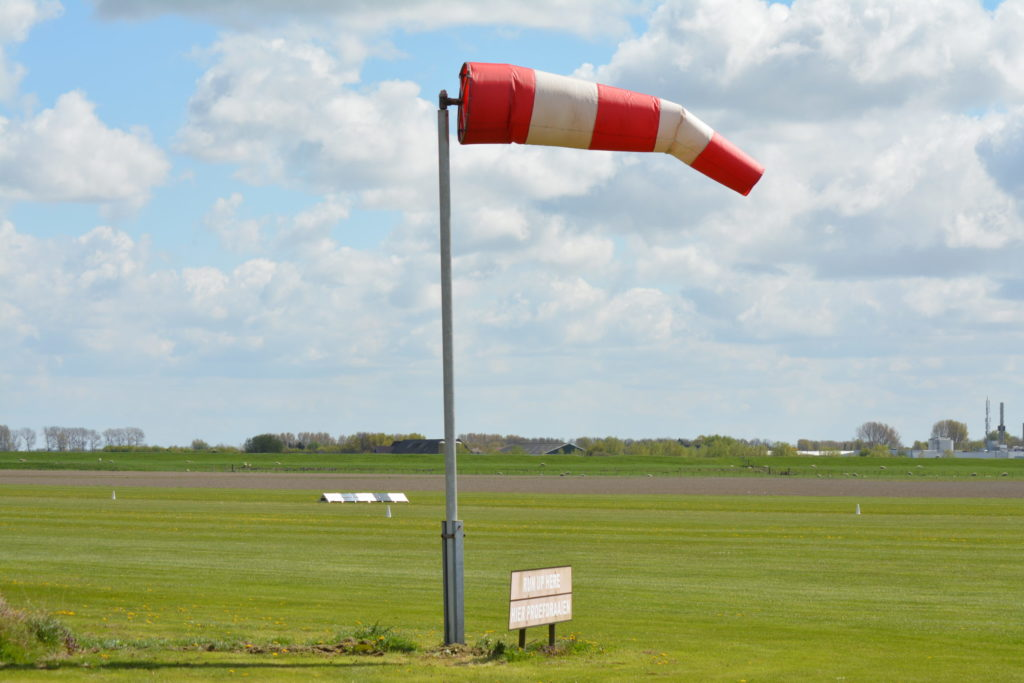 A red and white striped windsock at an airport runway