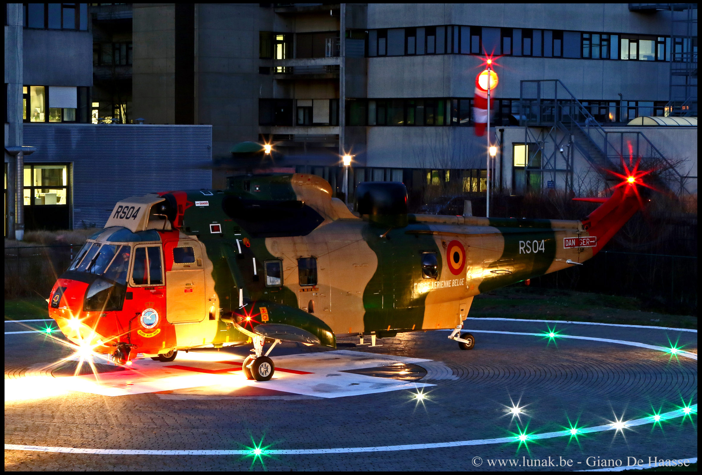 helicopter at dusk with internally lighted windsock assembly in the background next to the hospital.